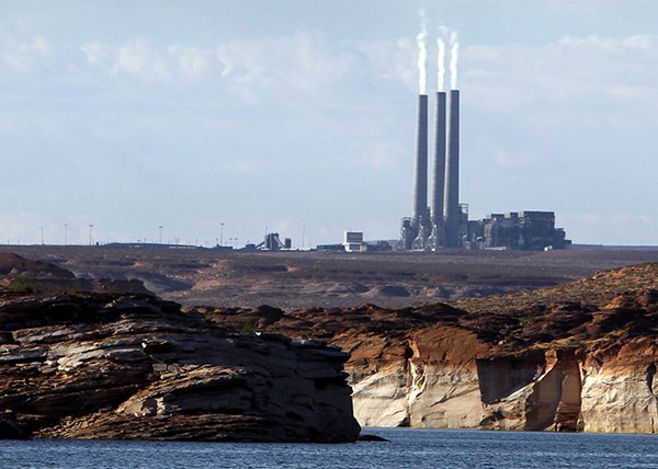 FILE - This Sept. 4, 2011 file photo shows the main plant facility at the Navajo Generating Station, as seen from Lake Powell in Page, Ariz. The federal government is proposing new limits for pollution from the coal-fired power plant on the Navajo Nation that it says will improve visibility at places like the Grand Canyon, but it could come with a price tag of more than $1 billion, according to the plant's owners. (AP Photo/Ross D. Franklin, File)