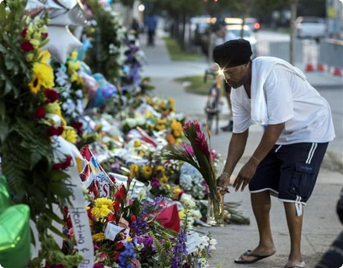A man lays flowers on a memorial on the sidewalk outside the Emanuel AME Church, Saturday, June 20, 2015 in Charleston, S.C. People started visiting the site well before sunrise four days after a gunman shot and killed nine people during a Bible study session at the church Wednesday night. (AP Photo/Stephen B. Morton)