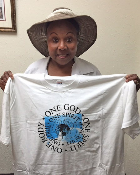 Sister Malaika Evans displays the One God – One Spirit – One Body t-shirt. (Cora J. Fossett photo)