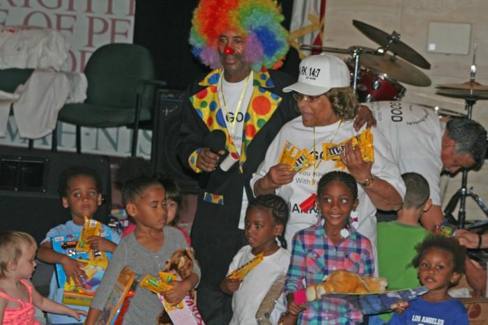 Brian Ferguson, as 'Christian the Clown,' distributes toys to children.