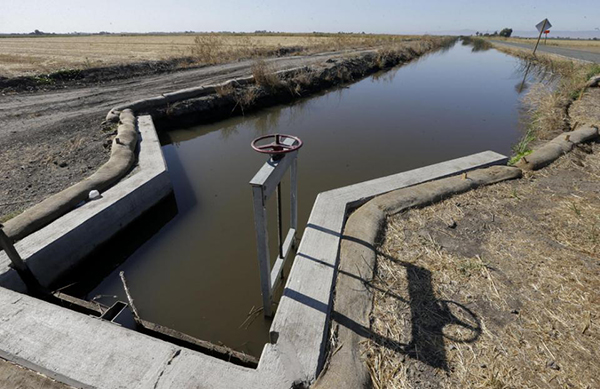 In this photo taken July 15, 2015, water flows down a canal near Byron, Calif. The California State Water Resources Control Board said it's proposing a fine of $1.5 million against the Byron-Bethany Irrigation District for allegedly taking water from a pumping plant after it was warned that there was not enough water. (AP Photo/Rich Pedroncelli)