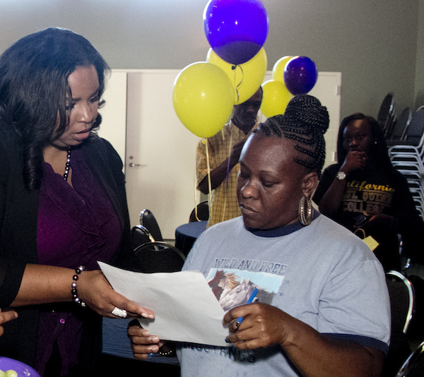 Recruiting Specialist Nicole Fords explains financial aid and registration information to a parent of a student heading to Paul Quinn College in the fall.