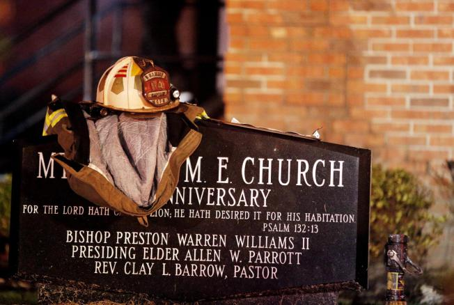A firefighter's jacket and helmet sit on a marker outside Mount Zion African Methodist Episcopal church, early Wednesday, July 1, 2015, in Greeleyville, S.C. The African-American church, which was burned down by the Ku Klux Klan in 1995, caught fire Tuesday night, June 30, 2015. (Veasey Conway/The Morning News via AP)