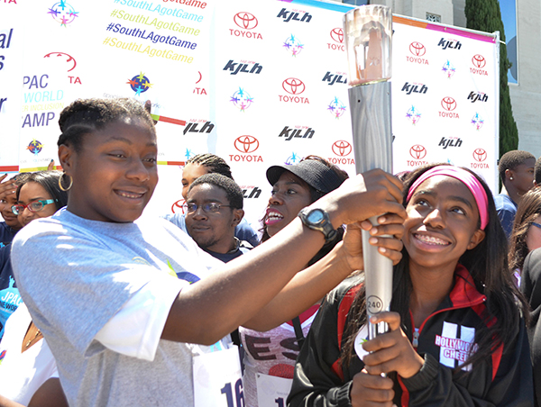 Breanna Clark (left) and Irene Green (right) hold the torch from the 1992 Olympic Games. (Amanda Scurlock/ LA Sentinel)