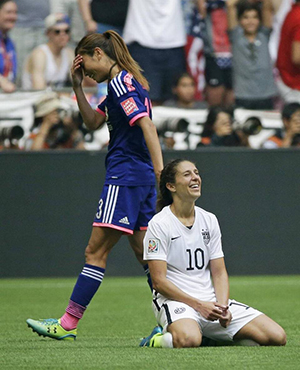 United States' Carli Lloyd kneels as Japan's Rumi Utsugi, left, walks off after the U.S. beat Japan 5-2 in the FIFA Women's World Cup soccer championship in Vancouver, British Columbia, Canada, Sunday, July 5, 2015. (AP Photo/Elaine Thompson)