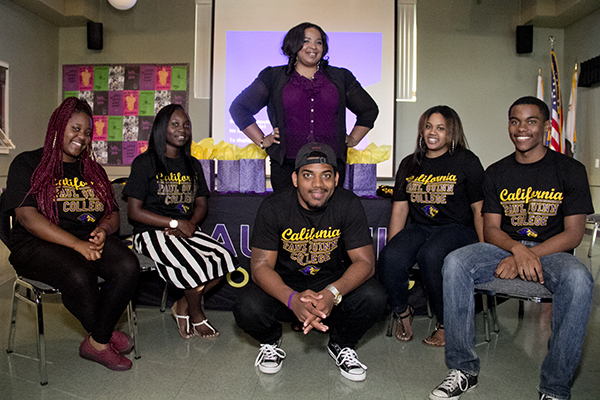 Nicole Ford (center, standing) poses with a few of the students that she got scholarships for, to attend Paul Quinn College. (Troy Tieuel/LA Sentinel)