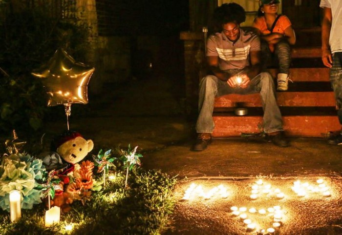Chris Ball-Bey sits at the candlelight memorial for his brother Mansur Ball-Bey, the 18-year-old who was fatally wounded in an officer-involved shooting Wednesday in the Fountain Park Neighborhood. (Lawrence Bryant/St. Louis American)