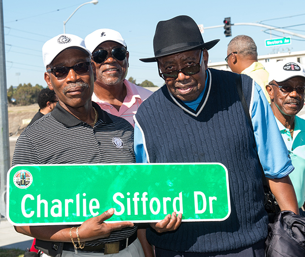 Charles Sifford, Jr. displays the new street sign that bears his late father's name. Charlie Sifford's caddy, Jimmy Green, stands next to him. (Courtesy Photo)