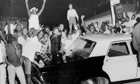 13-year old Bilal Ali, center in white shirt, is hoisted above the crowd by his uncle so he can see the unrest, at 103rd Streets and Central Avenue in Watts. (File photo)