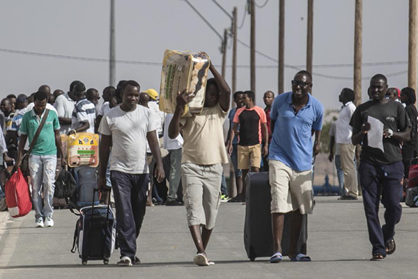 """African illegal migrants walk out of the Holot detention center in the Negev desert in southern Israel, Tuesday, Aug. 25, 2015. Since it passed a 2012 """"anti-infiltration"""" law, Israel has sent 1,700 migrants to the Holot facility deep in Israel's Negev desert. Israel's Supreme Court upheld the law in the latest hearing but ruled that migrants held at Holot for more than 12 months must be freed. About 1,200 migrants are being released beginning Tuesday. (AP Photo/Tsafrir Abayov)"""