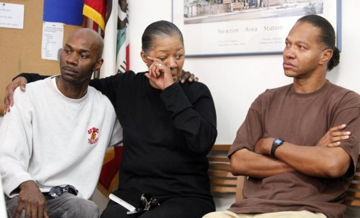 Elizabeth Peterson, center, and her two sons: David White, left, and Anthony White, grieve in 2010 for her older son, Herbert Tracy White, whose body parts were found in a backpack.