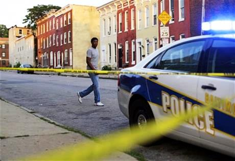 In this July 30, 2015 picture, a man walks past a corner where a victim of a shooting was discovered in Baltimore. Murders are spiking again in Baltimore, three months after Freddie Gray's death in police custody sparked riots. This year's monthly bloodshed has twice reached levels unseen in a quarter-century. In May, Baltimore set a 25-year high of 42 recorded killings. After a brief dip in June, the homicide is soaring again. (AP Photo/Patrick Semansky)