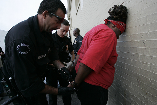 Los Angeles Police officers with the Central Area move in to arrest a homeless woman sleeping on a sidewalk in the Skid Row area of downtown Los Angeles, Tuesday, Oct. 10, 2006.  Starting this month, a beefed-up police force is arresting people who violate a daytime sidewalk sleeping ban.   (AP Photo/Damian Dovarganes)