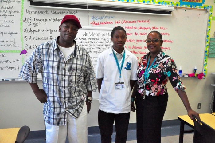 Caption: Parent Lee Trimble (left) visited his son Reginald's (center) English Language Arts class where he met with instructor Mona Walker (right) and participated in an analytical writing exercise.