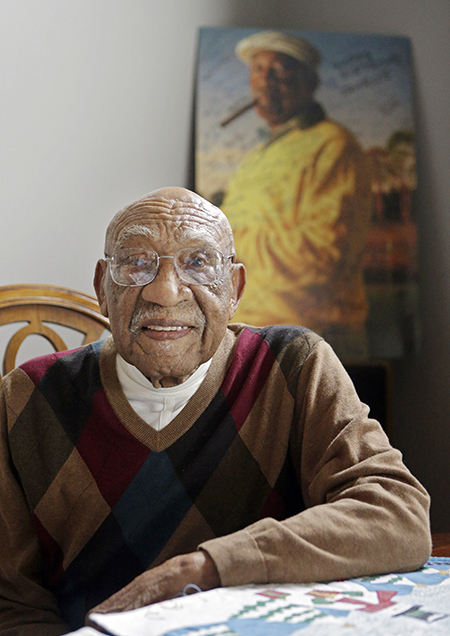 In this Nov. 13, 2014 file photo former PGA golfer Charlie Sifford sits in the dining room in his home in Brecksville, Ohio. Authorities say the son and ex-daughter-in-law of the late black golfing pioneer Sifford have been indicted on charges related to the theft of more than $1 million from him. Craig and Sandra Sifford were charged Tuesday, July 28, 2015 with theft, money laundering and unauthorized use of property. Both are 48. The Cuyahoga County prosecutor's office says they spent Sifford's money on travel, dining, clothes, jewelry and landscaping. (AP Photo/Mark Duncan, File)