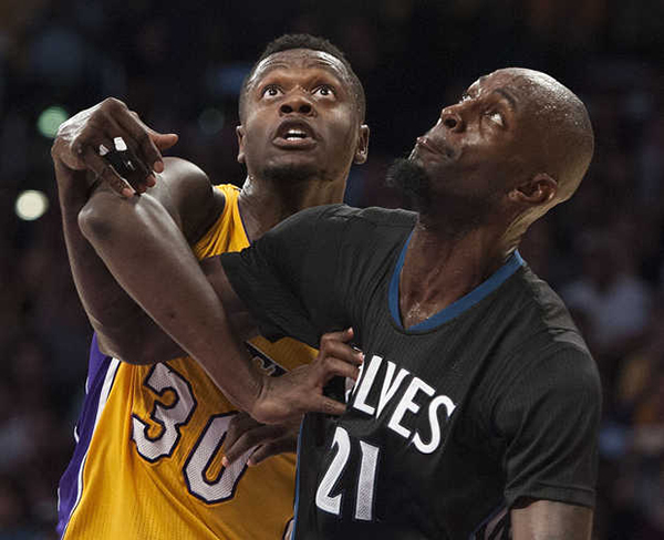 Los Angeles Lakers' Julius Randle, left, works for position against Minnesota Timberwolves' Kevin Garnett during the first half of an NBA basketball game Wednesday, Oct. 28, 2015, in Los Angeles. The Timberwolves won 112-111. (KEVIN SULLIVAN — AP)