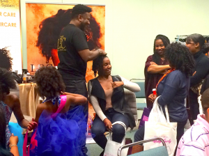 Lawrence Ray Parker II, the CEO and founder of Lawrence Ray Concepts, a natural organic line of hair products (pictured doing hair). Afrolicious Hair Expo brings together Black women of southern California. (Shannen Hill photo)