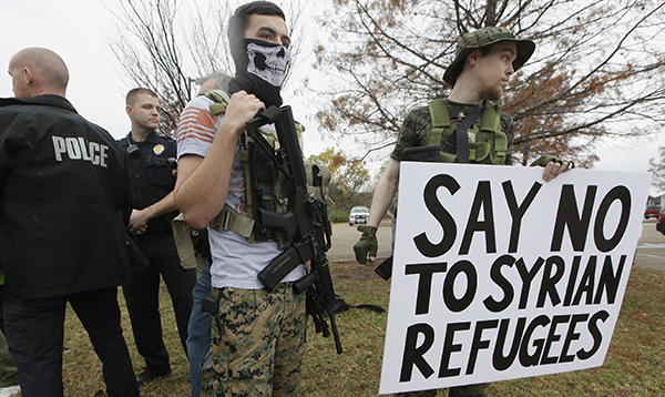 As police stand guard, armed anti-Muslim protestors, who did not want to give their names, stand across the street from a mosque during a demonstration in Richardson, Texas, on Saturday, Dec. 12, 2015. (AP Photo/LM Otero)