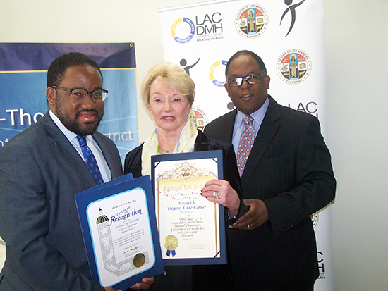 Assembly member Sebastian Ridley-Thomas (left) and County Supervisor Mark Ridley-Thomas (right) present Luana Murphy (center), president of Exodus Recovery and operator of WMHUCC with proclamations for her outstanding work in the area of mental health.