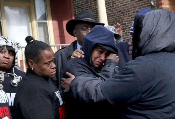 Janet Cooksey, center, the mother of Quintonio LeGrier, is comforted by family and friends during a news conference to speak out about Saturday's shooting death of her son by the Chicago police, on Sunday, Dec. 27, 2015, in Chicago. Grieving relatives and friends of two people shot and killed by Chicago police said Sunday that the city's law enforcement officers had failed its residents. (Nancy Stone/Chicago Tribune via AP)