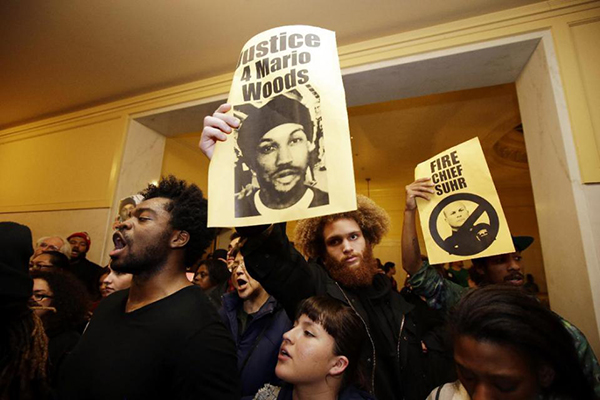 Demonstrators hold signs outside of a crowded police commission hearing inside city hall Wednesday, Dec. 9, 2015, in San Francisco. San Francisco's police chief wants city officials to arm his department with Tasers amid continued protests over the shooting death of Mario Woods, who was wielding a knife when he was shot by police. (AP Photo/Marcio Jose Sanchez)