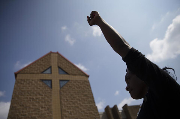 In this Tuesday, July 28, 2015 file photo, mourner JeRee Wilson holds her fist in the air outside funeral services for Samuel Dubose at the Church of the Living God in the Avondale neighborhood of Cincinnati. Dubose was fatally shot by a University of Cincinnati police officer who stopped him for a missing license plate. Volatile, racially sensitive questions of whether to charge police officers for fatal on-duty shootings, and whether jurors will convict an officer in such a case, hang over two of Ohio's largest cities. (AP Photo/John Minchillo, File)