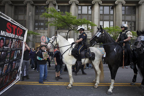 In this Saturday, May 23, 2015 photo, mounted police officers follow demonstrators as they march through downtown during a protest against the acquittal of Michael Brelo, a patrolman charged in the shooting deaths of two unarmed suspects, in Cleveland. Brelo was acquitted Saturday in a case involving a 137-shot barrage of gunfire. Volatile, racially sensitive questions of whether to charge police officers for fatal on-duty shootings, and whether jurors will convict an officer in such a case, hang over two of Ohio's largest cities. (AP Photo/John Minchillo, File)