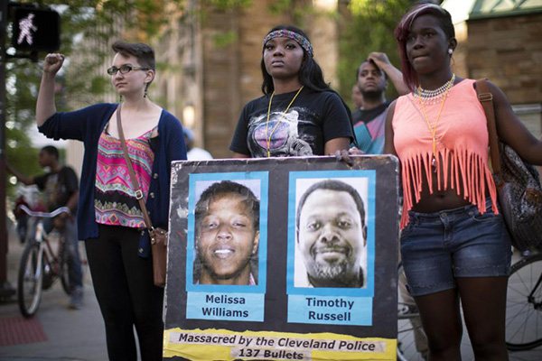 In this Saturday, May 23, 2015, file photo, demonstrators pause to stand in solidarity during a protest against the acquittal of Michael Brelo, a patrolman charged in the shooting deaths of two unarmed suspects in Cleveland. Brelo was acquitted Saturday in a case involving a 137-shot barrage of gunfire. Volatile, racially sensitive questions of whether to charge police officers for fatal on-duty shootings, and whether jurors will convict an officer in such a case, hang over two of Ohio's largest cities. (AP Photo/John Minchillo, File)