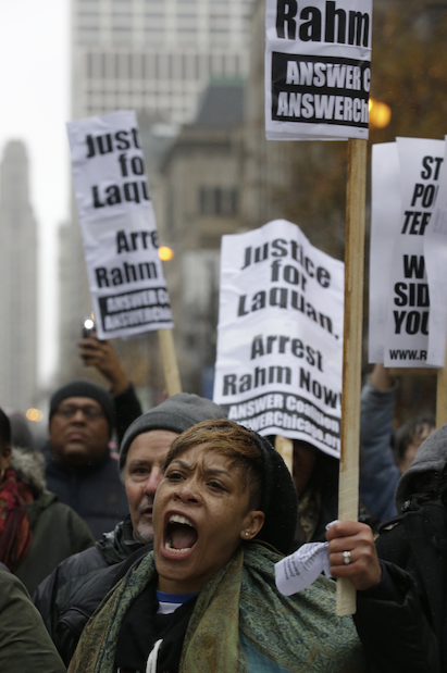 4-In this Tuesday, Nov. 24, 2015, file photo, a protester holds a sign as people rally for 17-year-old Laquan McDonald, who was shot 16 times by Chicago Police Department Officer Jason Van Dyke in Chicago. McDonald, whose name demonstrators are shouting as they march the streets and plan to shut down the city's glitziest shopping corridor on Friday, lived a troubled life full of disadvantages and at least one previous brush with the law. (AP Photo/Paul Beaty, File)