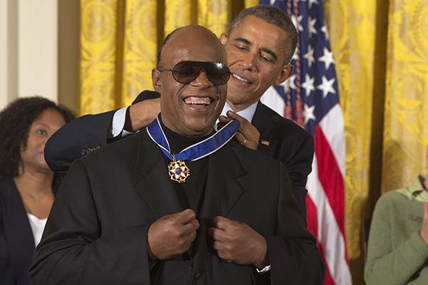 Musician Stevie Wonder celebrates as President Barack Obama awards him the Presidential Medal of Freedom, Monday, Nov. 24, 2014, during a ceremony in the East Room of the White House in Washington.  President Obama is presenting the nation's highest civilian honor to 19 artists, activists, public servants and others.  (AP Photo/Jacquelyn Martin)