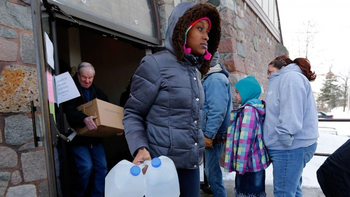 Genetha Campbell carries free water being distributed at the Lincoln Park United Methodist Church in Flint, Mich, (AP Photo/Paul Sancya)