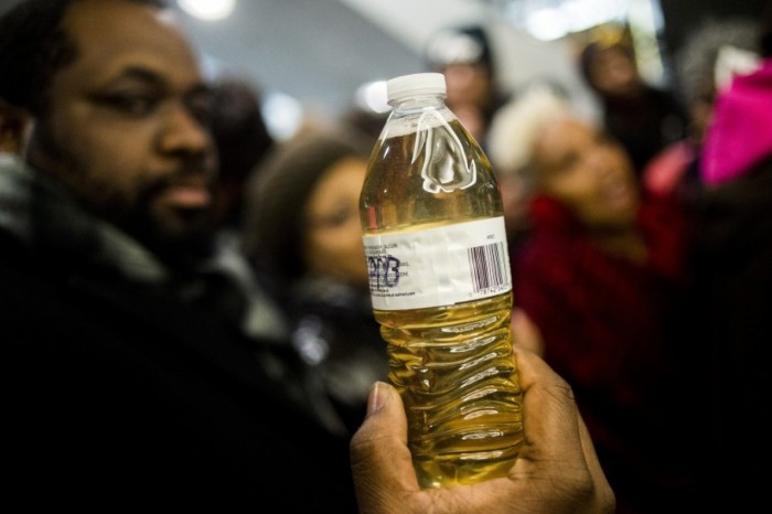 The Rev. David Bullock on Thursday holds a bottle of Flint water outside of the Romney Building, home to Gov. Rick Snyder's office in Lansing. (Jake May/The Flint Journal-MLive.com/AP)