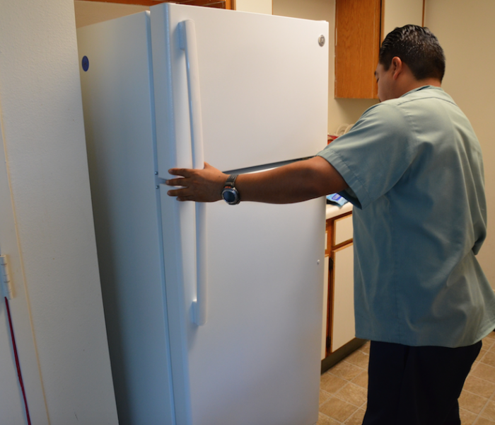 A representative from ARCA installs a brand new Energy Star® refrigerator in a FAME Gardens apartment. Residents can expect to save up to $60 per year on refrigerator operating costs as these units use half the electricity of non-Energy Star® models.
