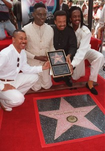 "Ralph Johnson, Phillip Bailey, Maurice White and Verdine White, members of the original Earth, Wind & Fire musical group, hold up a miniature Hollywood Walk of Fame star as they are honored with the 2,053rd ""shining star"" on Hollywood Boulevard Thursday, Sept. 14, 1995, in Los Angeles. (AP Photo/Kevork Djansezian)"