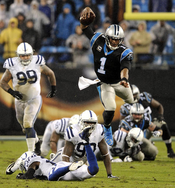 FILE - In this Nov. 2, 2015, file photo, Carolina Panthers' Cam Newton (1) leaps over Indianapolis Colts players during an NFL football game in Charlotte, N.C. Newton's spectacular season has earned him The Associated Press NFL Offensive Player of the Year award. (AP Photo/Mike McCarn, File)