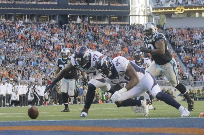 Broncos DeMarcus Ware (94) and Malik Jackson (97) Recover Panther Fumble.  Photo:  Associated Press