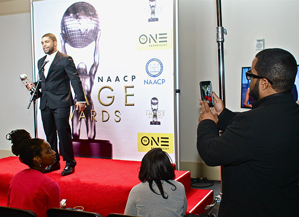 "Actor and Musician Ice Cube snaps photo of son O'Shea Jackson Jr. as he talks about winning his award for outstanding actor in a motion picture for his role in ""Straight Outta Compton"". (Mesiyah McGinnis/LA Sentinel)"