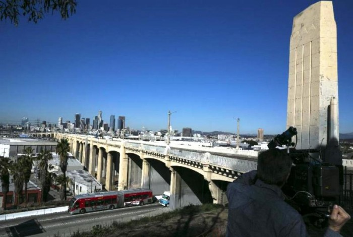 In this Wednesday, Feb. 3, 2016, photo The 6th Street Bridge that spans the Los Angeles River is seen in Los Angeles, before it is closed permanently for demolition. The landmark bridge, dating to the 1930's, is being replaced due to deterioration caused by a chemical reaction in the concrete. The $449 million project to build a replacement bridge, designed by architect Michael Maltzan, is expected to be completed by 2019 at the earliest. (AP Photo/Damian Dovarganes)
