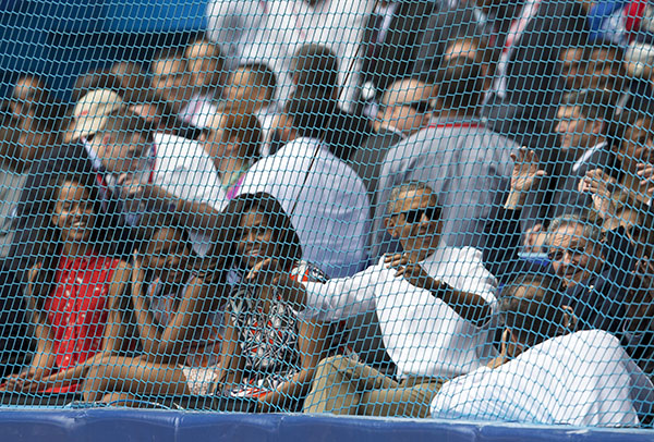 Cuban President Raul Castro, right, cheers next to U.S. President Barack Obama, his wife Michelle, and their daughters Sasha and Malia, at the start of a baseball game between the Tampa Bay Rays and the Cuban national baseball team, in Havana, Cuba, Tuesday, March 22, 2016. The crowd roared as Obama and Cuban President Raul Castro entered the stadium and walked toward their seats in the VIP section behind home plate. It's the first game featuring an MLB team in Cuba since the Baltimore Orioles played in the country in 1999. (Ismael Francisco/Cubadebate via AP)