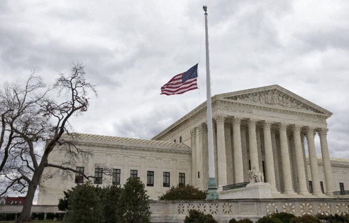 In this Feb. 25, 2016, file photo, in honor of Justice Antonin Scalia, a flag in the Supreme Court building's front plaza flies at half-staff in Washington. African-American voters see the Republican opposition to President Barack Obama filling the Supreme Court vacancy as the latest affront to the first black president. Obama isn't on the ballot this fall, but plenty of Republicans are. (AP Photo/J. Scott Applewhite, File)