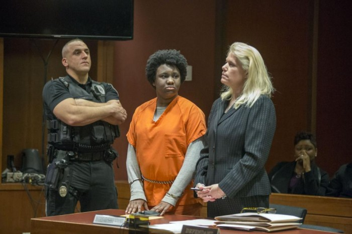 With her mother Juana Sully seated behind her, Hyphernkemberly Dorvilier, stands between a sheriff's deputy and her defense attorney Karen Thek as she listens to the charges against her. (Ed Hille/The Philadelphia Inquirer via AP)