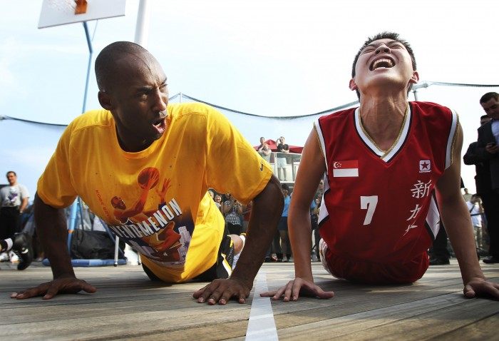 Los Angeles Lakers superstar Kobe Bryant, left, encourages a youth member of the Singapore Basketball Association to complete his set of push-ups during a basketball clinic on Saturday Sept. 17, 2011 in Singapore. Bryant says he's still considering playing overseas as an owners' lockout of players threatens to sabotage the upcoming NBA season. (AP Photo/Wong Maye-E)