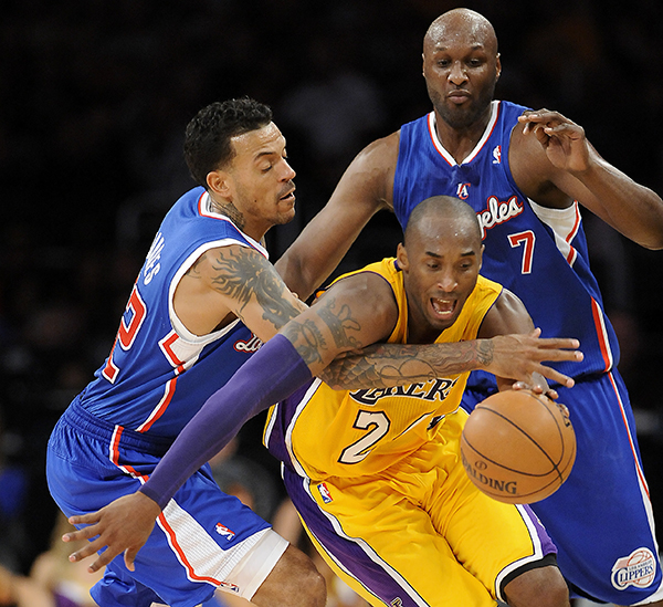 Los Angeles Lakers guard Kobe Bryant, center, is double teamed by Los Angeles Clippers forward Matt Barnes, left and Lamar Odom (7) in the second half of an NBA basketball game, Friday, Nov. 2, 2012, in Los Angeles. The Clippers won 105-95. (AP Photo/Gus Ruelas)