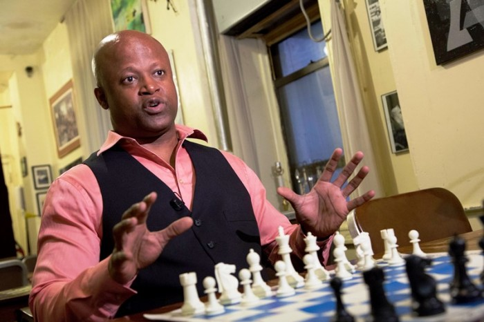 In this April 12, 2016 photo, chess grandmaster Maurice Ashley talks during an interview at Chess Forum in New York. The Brooklyn resident has been inducted to the World Chess Hall of Fame in St. Louis. (AP Photo/Mark Lennihan)