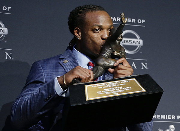 Alabama's Derrick Henry kisses the Heisman Trophy while posing for photos after winning the award as the country's top college football player, in New York on Dec. 12, 2015, (AP Photo/Julie Jacobson)