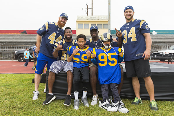 Los Angeles Rams players pose for a photo with students during the Los Angeles Rams play 60 event on May 13, 2016 in Inglewood, Calif. (Los Angeles Rams/Ric Tapia)