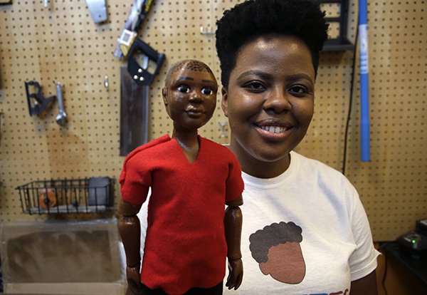 In this Tuesday, April 26, 2016 photo Jennifer Pierre, of Fort Lauderdale, Fla., a student at Babson College, holds her prototype doll named Jaylen in a workroom at the school, in Wellesley, Mass. Pierre is launching a new line of dolls intended for boys of color. Pierre says her company is a celebration of brown boyhood, meant to offer boys of all races dolls that looks like them. (AP Photo/Steven Senne)
