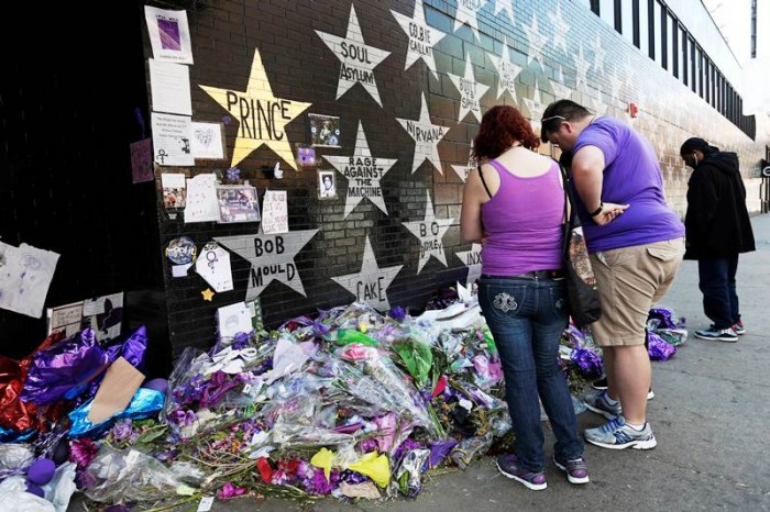 A star honoring Prince, now painted gold, stands out on the wall Thursday, May 5, 2016 as fans gathered at the memorial for the singer at First Avenue in Minneapolis where he often performed. The pop rock singer died on April 21 at the age of 57. (AP Photo/Jim Mone)