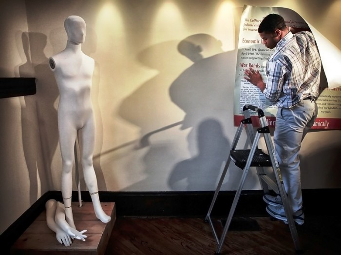 In this April 19, 2016 photo, St. George's student Noah Pope helps install an exhibit on the WWII era in Tennessee's Collierville at the city's Morton Museum. (Jim Weber/The Commercial Appeal via AP)