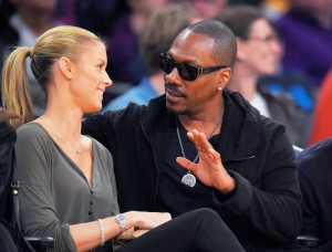 In this April 12, 2015, file photo, actor Eddie Murphy talks with his girlfriend Paige Butcher during an NBA basketball game between the Los Angeles Lakers and the Dallas Mavericks. (AP Photo/Mark J. Terrill, File)